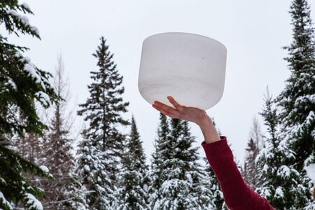 Man is holding his crystal bowl up in the air, outside in the winter. With blurry fir trees full of snow in the background Stockfoto