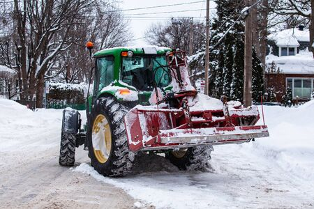 Red snowblower installed on a green tractor clearing snow from the streets after a winter storm
