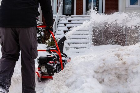Rear view of a man blowing snow and clearing the entrance of a house after a winter storm