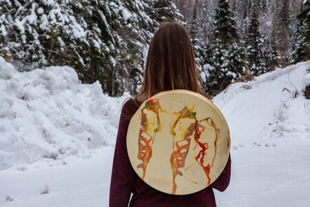 Woman is hiking a snowy forest with her sacred drum held on her back as a backpack Stockfoto - 133182946