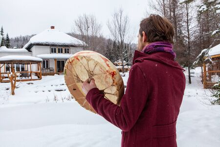 Young man dressed in urban red clothing, pictured from the back is playing his sacred drum with a drumstick. Pictured from the back, outside in winter