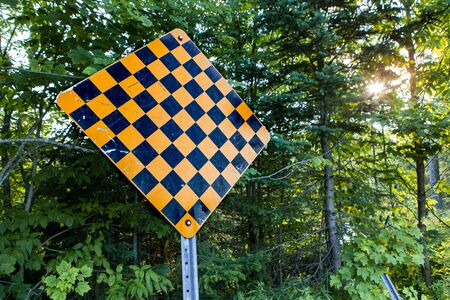 Picture taken against the light of the sun at sunset with a dead end yellow and black checkered sign Stock fotó - 133253537