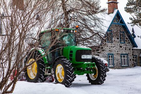 Obstructed view of a green tractor clearing snow in front of a house after a winter storm