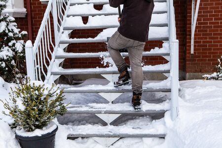 Rear view of a man shoveling snow and clearing the stairs in front of a house after a winter storm Фото со стока