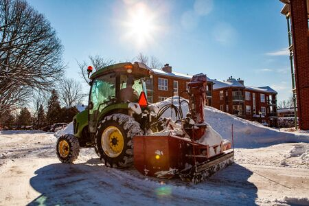 Red snowblower installed on a green tractor clearing snow from the streets after a winter storm, on a sunny day Stock fotó