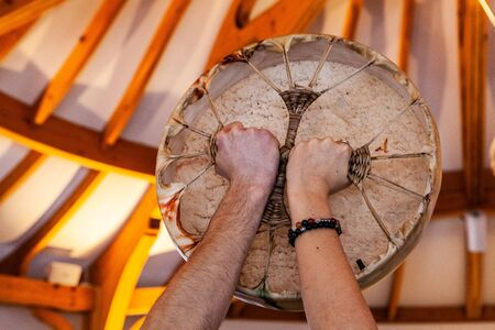 Closeup shot of the back side of sacred drum being held up by the hands of 2 people, with beautiful blurry wooden roof in the background