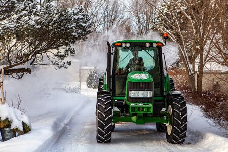 Front view of a green tractor clearing snow from the streets after a winter storm Stock fotó