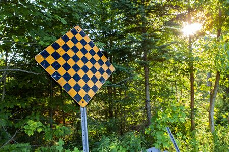 Wide angle picture taken against the light of the sun at sunset. Yellow and black checkered sign Stock fotó - 133253626