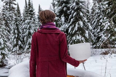 Man wearing red urban clothing is holding his crystal bowl in his right hand, outside in the winter. With snowy fir trees in the background
