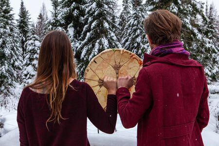 Couple is holding his crystal bowl up in the air, outside in the winter. With blurry fir trees full of snow in the background