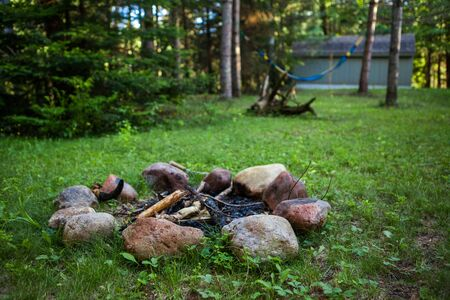 Campfire spot with a hammock hanging in the background. Wide angle picture showing a big part of the backyard