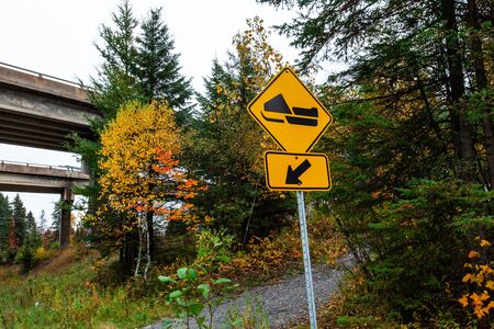 Picture taken in Quebec, Canada, while autumn colors were very present. Perspective from the side of the road with snowmobile track sign Stock fotó - 133253208