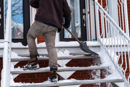 Rear view of a man shoveling snow and clearing the stairs in front of a house after a winter storm Stock Photo