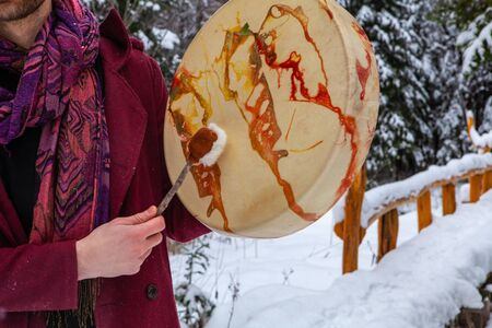 Young man wearing red urban clothing is playing his sacred drum with a drumstick. Pictured from the back, outside in winter