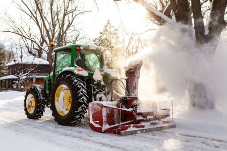 Red snowblower blowing snow installed on a green tractor clearing the streets after a winter storm, through the sun 免版税图像