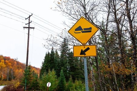 Picture taken in Quebec, Canada, while autumn colors were very present. Perspective from the side of the road with yellow snowmobile track sign