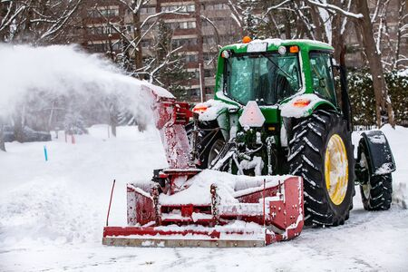 Red snowblower blowing snow installed on a green tractor clearing the streets after a winter storm
