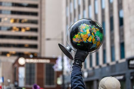 Man is holding a black globe as a sign in an ecological protest.