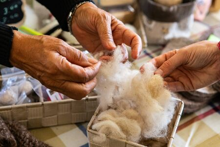 Selective focus on hands grabbing and feeling smoothness of raw white wool inside wood basket at market place. Minerve farmers market