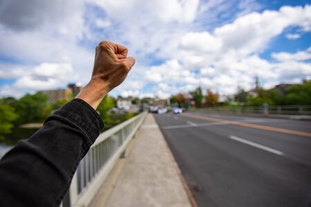 First person perspective and Selective focus on man fist raised during an ecological protest. Crowd of people walking against climate change