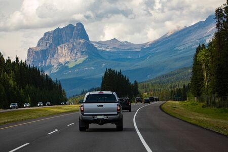 cars, pickups and SUVs are traveling accross the canadian rockies on a 4 lane highway. High mountain peaks and dense clouds in the background Imagens