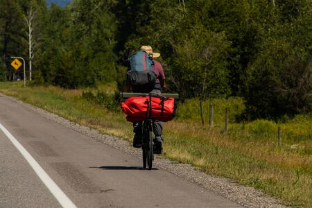 Man from the back traveling on bicycle, prepared with backpack and luggage for his long journey. Natural environment in the background.