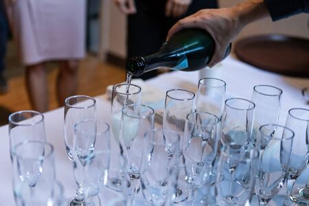 Selective focus of a person pouring in alcoholic drinks in to empty crystal glasses standing on a white clothed buffet table Stok Fotoğraf