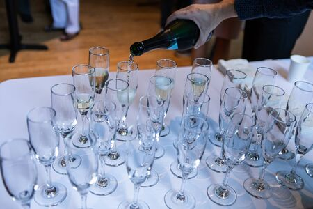 Selective focus of person pouring in wine and champagne in to crystal glasses standing on top of a white buffet table
