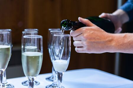 Close up photo of a person pouring in wine and champagne in empty crystal glasses that are standing on a white clothed buffet table Stok Fotoğraf - 133960549