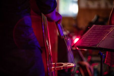 Close up photo of a person in font of an audience and paper music sheets playing a special string type instrument