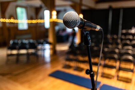 Close up photo of a microphone standing on stage in an empty music hall room with bokeh lights on the left side Stok Fotoğraf - 133960611