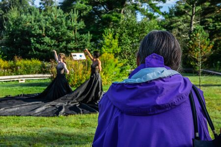 Selective focus of the back of adult female watching a artistic couple performing yoga in a natural park on a sunny day