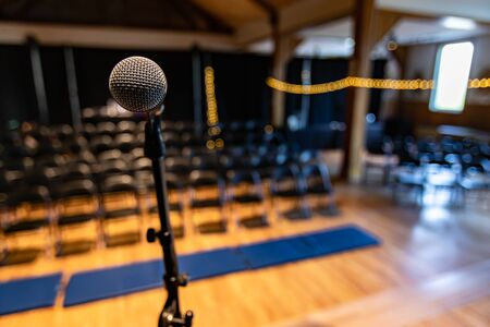 Close up photo of silver microphone on stage of an empty concert hall room with bokeh lights on the right Stok Fotoğraf - 133960777