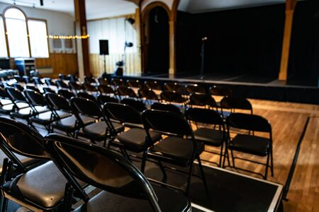Selective focus of theater or concert hall with empty seats standing in a row and empty podium stage Stok Fotoğraf