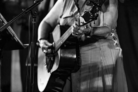 Black and white photo taken of an adult person making music while playing songs on a classical acoustic guitar