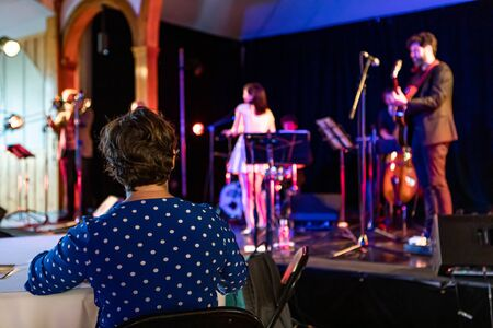 Backside view photo of a person sitting alone while watching and listening to a live performance of a group of musicians Stock fotó
