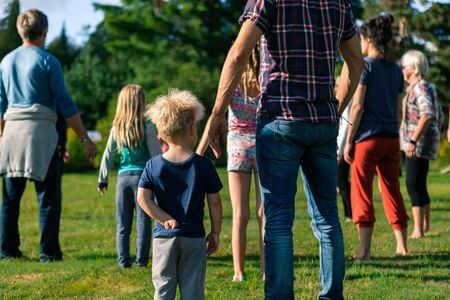 Selective focus and behind view of group of people with young children standing in a grass field on a sunny day Standard-Bild - 133961192