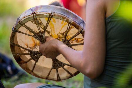 Cerca de las manos del hombre mientras toca el tambor sagrado durante un ritual espiritual, sosteniendo el tambor nativo americano durante una celebración musical Foto de archivo