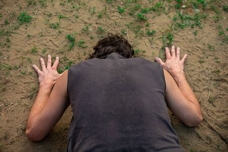 close up and high angle view of a man in a kneeling and bent forward facing pose, facing The soil of the earth during a yoga session in nature