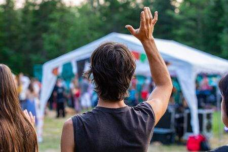 A young caucasian man is seen from behind with one arm raised in air during a shamanic exercises, diverse people enjoy spiritual gathering in the background