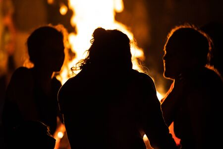 silhouette of group of people sitting in the front of the fire as they talk, seen from behind during dark night campfire, blurred background