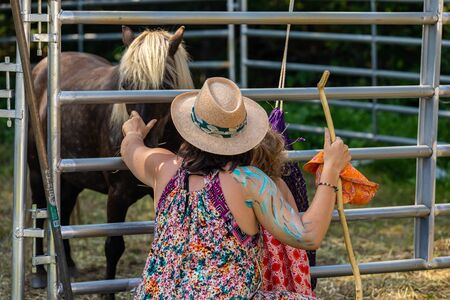 close up and back view of woman and his child playing with a beautiful brown horse behind the barrier