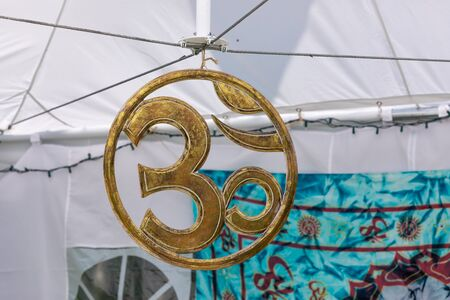 selective focus and close up of Hindu om symbol made out of metal, Hanging on the tent during a spiritual gathering with copy space