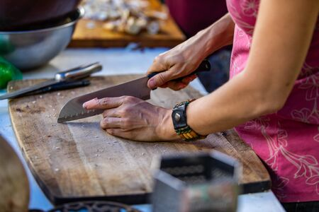 Woman responsible of a festival camp kitchen is seen from the left as she cuts vegetables on a big wooden slate of wood with a chopping knive. Stockfoto