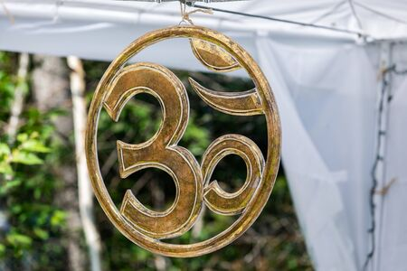selective focus and close up of Hindu om symbol made out of metal, Hanging on the tent during a spiritual gathering with copy space Reklamní fotografie - 133961820