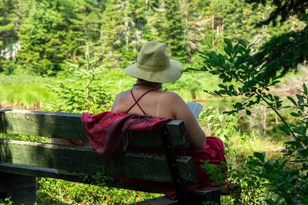 old woman reading a book in beautiful nature, wearing summer hat and enjoying a beautiful sunny day by the river, seen from behind