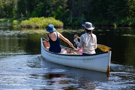 mother and daughter and the granddaughter are seen from the back as they riding small wooden boat and Rowing on the lake, with blurred trees on the background