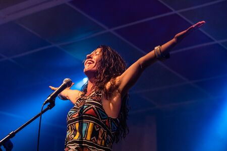 a female musician is viewed from a low angle as she sings and smiling with the audience with her hands raised up during a performance