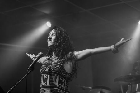 a female musician is viewed from a low angle as she sings and performs with hands raised and closed eyes, in black and white with copy space Фото со стока