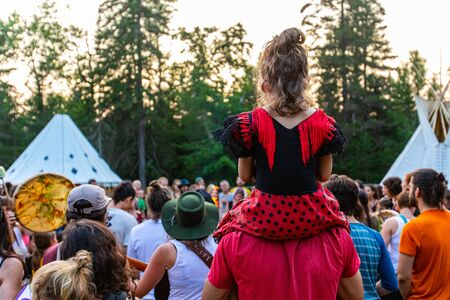 back view of a father holding his daughter on his shoulders, with a group of people crowded during spiritual gathering in woodland